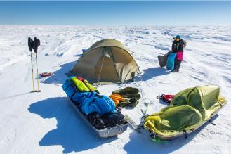 Il est 22h. Le campement est installé pour la nuit. Un point vert dans l'immensité blanche. Le soleil, lorsqu'il ne disparait pas derrière un voile nuageux, réchauffe un peu l'intérieur de la tente, pas autant toutefois que le réchaud que nous utilisons pour faire fondre la glace nécessaire à nos besoins en eau (environ 4 litres par jour et par personne).